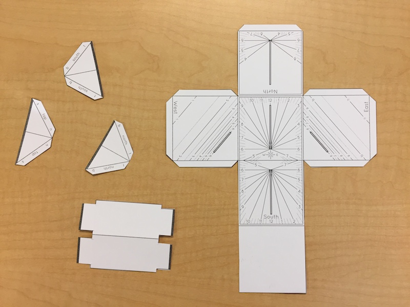 The cut out parts of a paper cube sundial